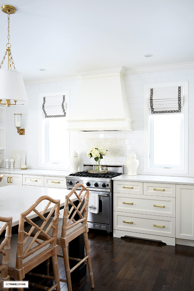 White kitchen with windows flanking the custom range hood, roman shades with ribbon detail.