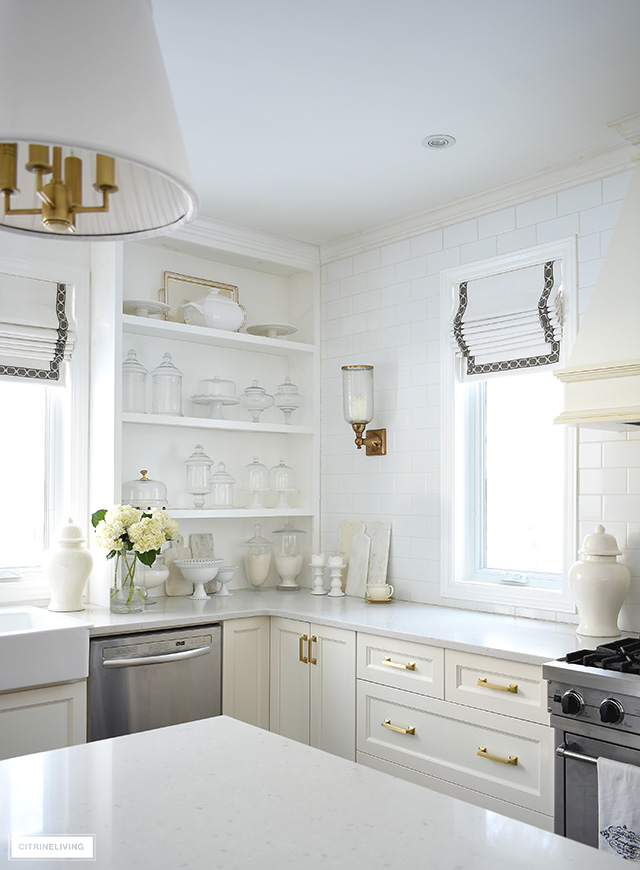 White kitchen with builtin open shelves, brass hardware and lighting, roman shades with ribbon detail.