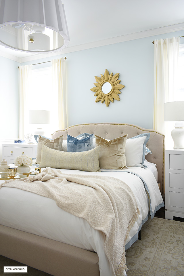 Bedroom update with three drawer nightstands, white ginger jar lamps, beige transitional rug and gorgeous white and blue bedding.