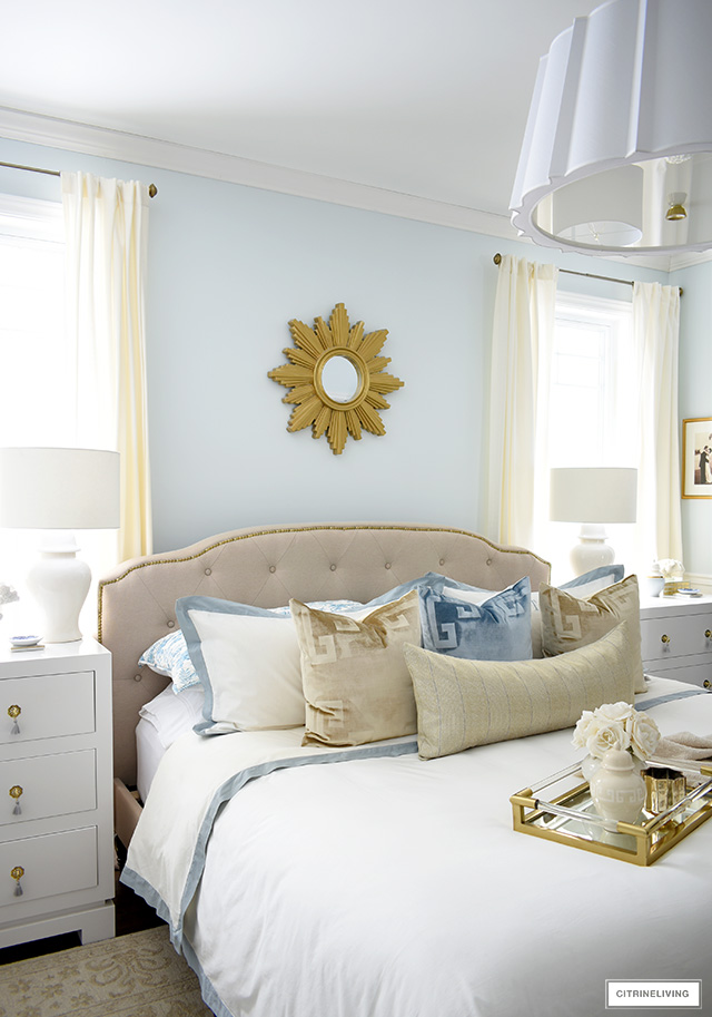 Chic master bedroom with upholstered bed, layered bedding ginger jar lamps and chic three drawer nightstands.