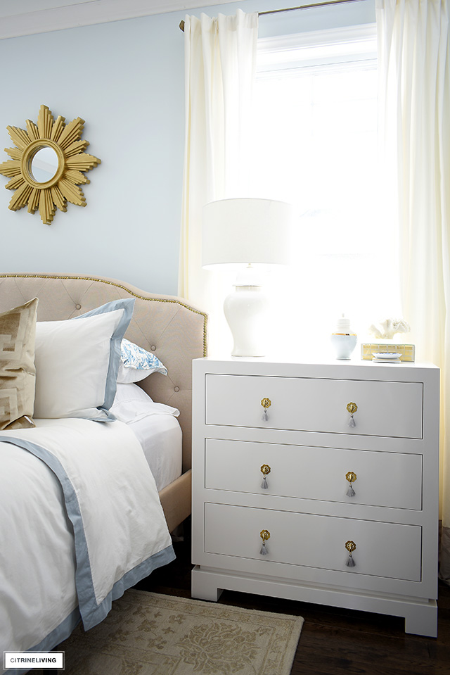 Chic and elegant three drawer nightstand with brass hardware and tassel pulls.