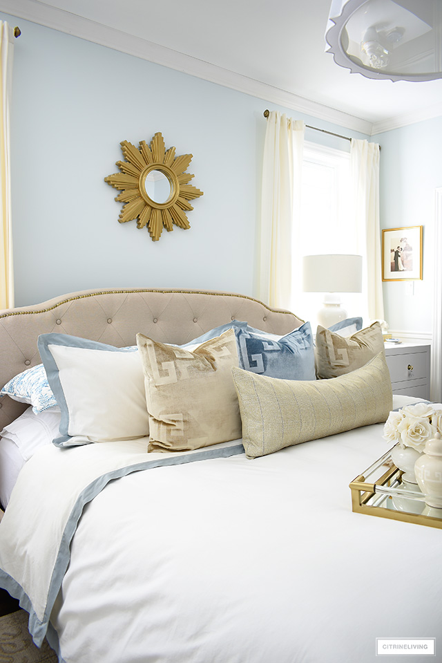 Beautiful upholstered bed layered with velvet pillows and luxe white bedding.