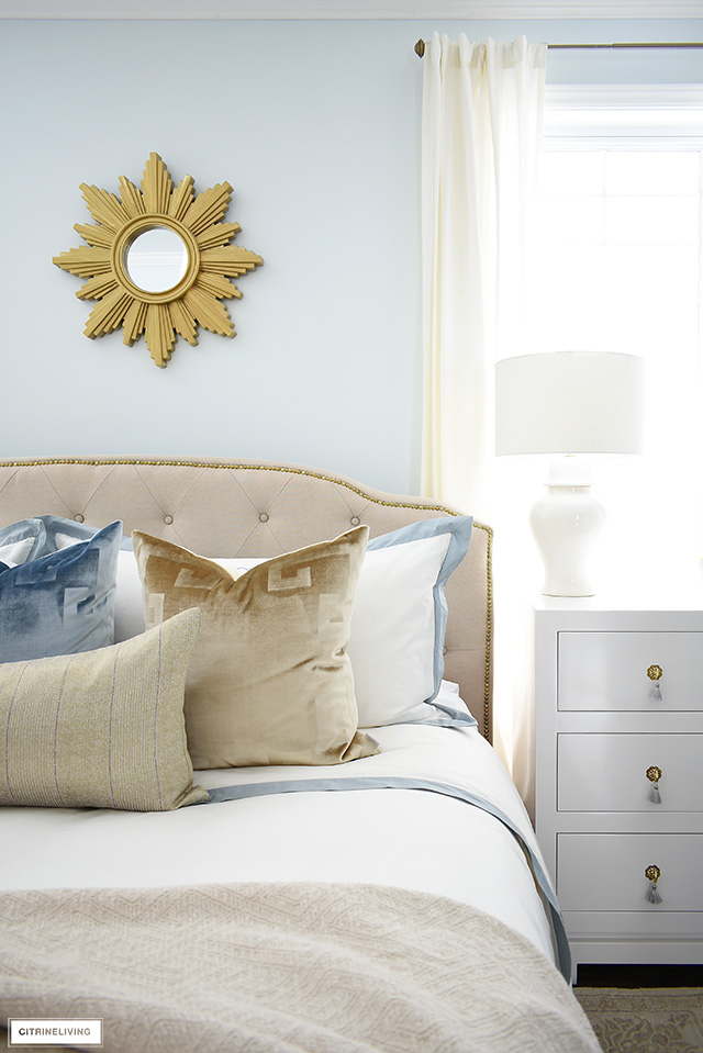 Beautiful master bedroom with soft blue, gold and white pieces creates a luxe and sophisticated look.