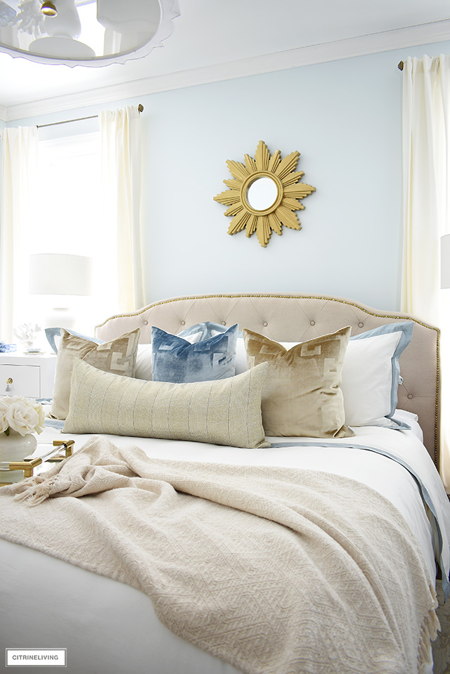 Beautiful master bedroom with upholstered headboard and brass nailhead trim. Layered bedding with velvet pillows.