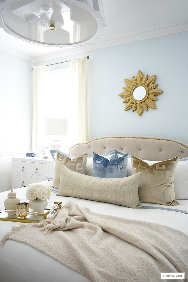 Gorgeous upholstered bed white classic white bedding, layered velvet pillows.