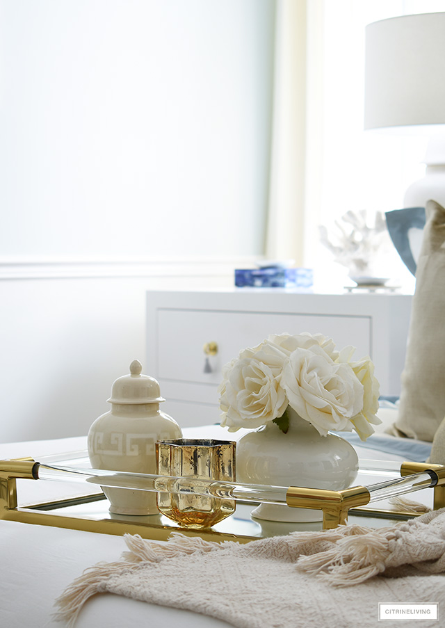 A pretty brass tray with faux roses, ginger jar and candle.