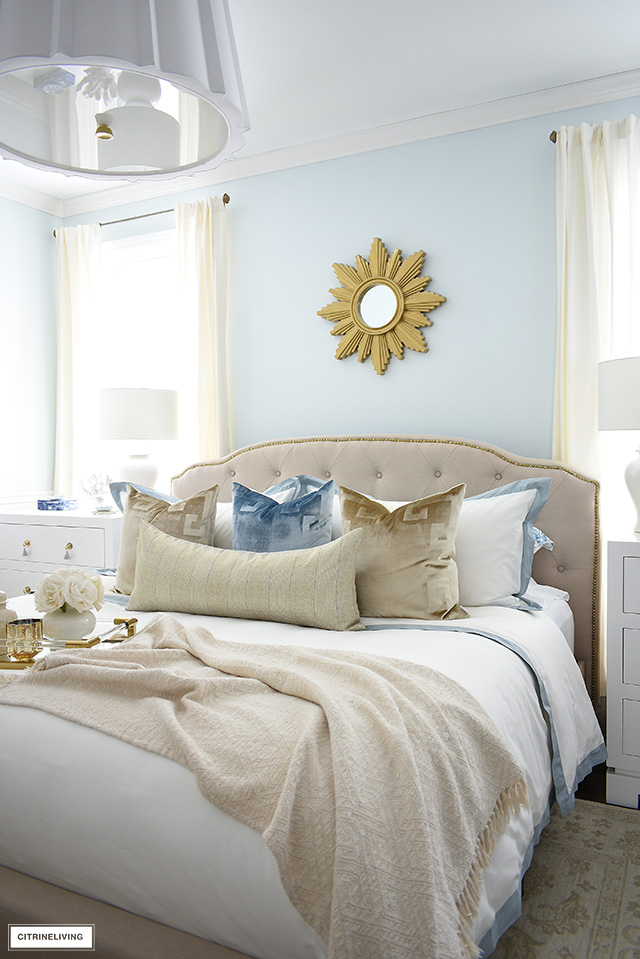Upholstered bed with brass nailhead trim, layered with white bedding and luxe velvet pillows.