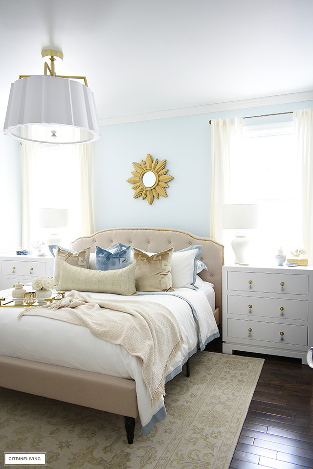 Beautiful master bedroom, upholstered bed with brass nailhead trim, three drawer nightstands and glamorous velvet pillows.