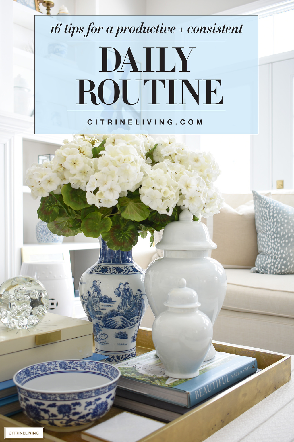 Beautiful blue and white vase with faux white floral arrangement paired with pale blue ginger jars.