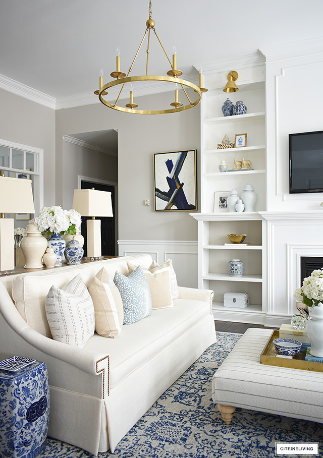 Living room decorating for spring with beautiful pillows, ginger jars, blue and white accents and faux floral arrangements.