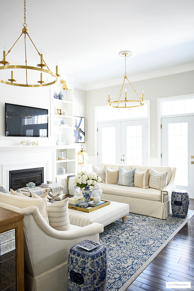 Spring living room decorating with gorgeous pillows, faux flowers and blue and white accents.