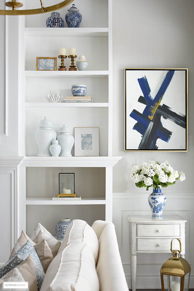 Beautiful spring bookshelves with ginger jars, coral, framed art and blue and white acceorries.