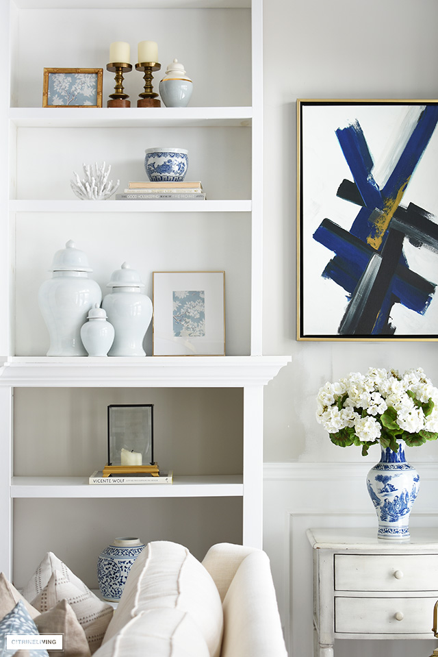 Beautiful bookshelf styling for Spring with ginger jars, framed art, blue and white accents.