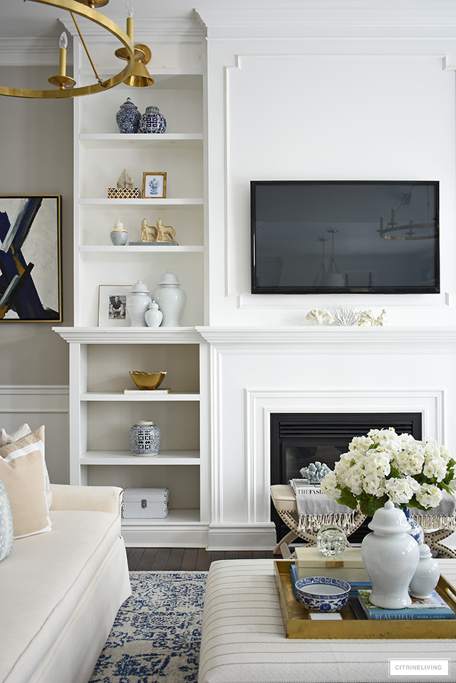 Spring decorating ideas for bookshelves with ginger jars, blue and white pottery and brass accents.
