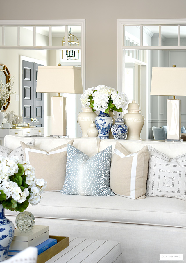 Gorgeous Spring living room decor with blue and white jars, faux flowers and gorgeous throw pillows.