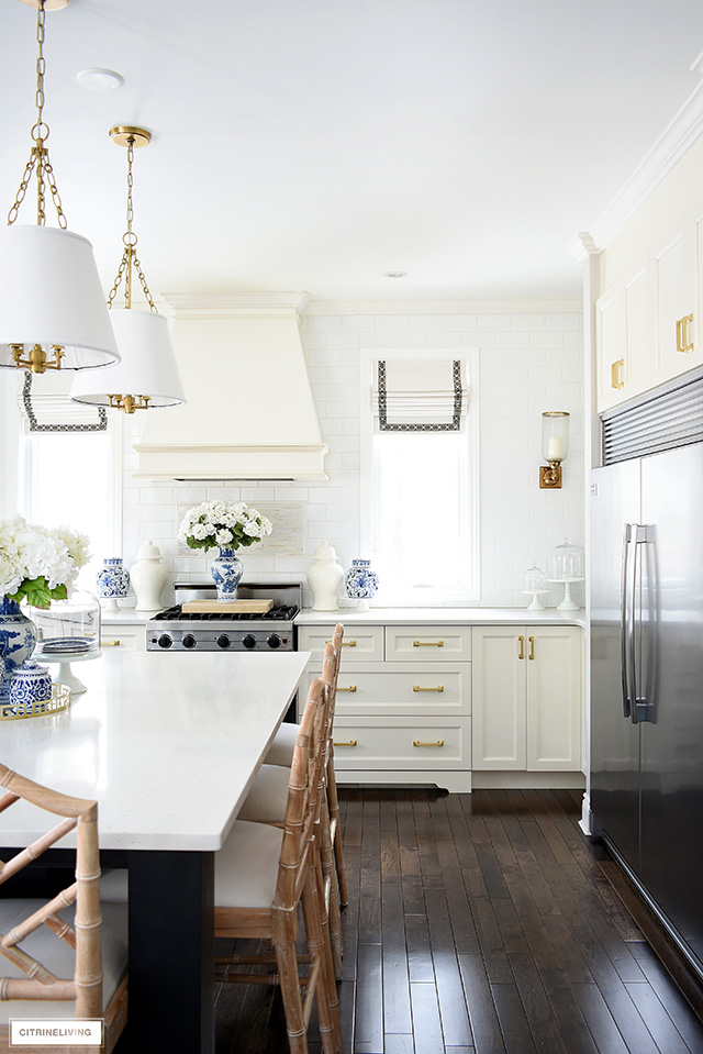 A gorgeous spring decorated kitchen with touches of blue and white pieces and faux flowers for a fresh and vibrant look.