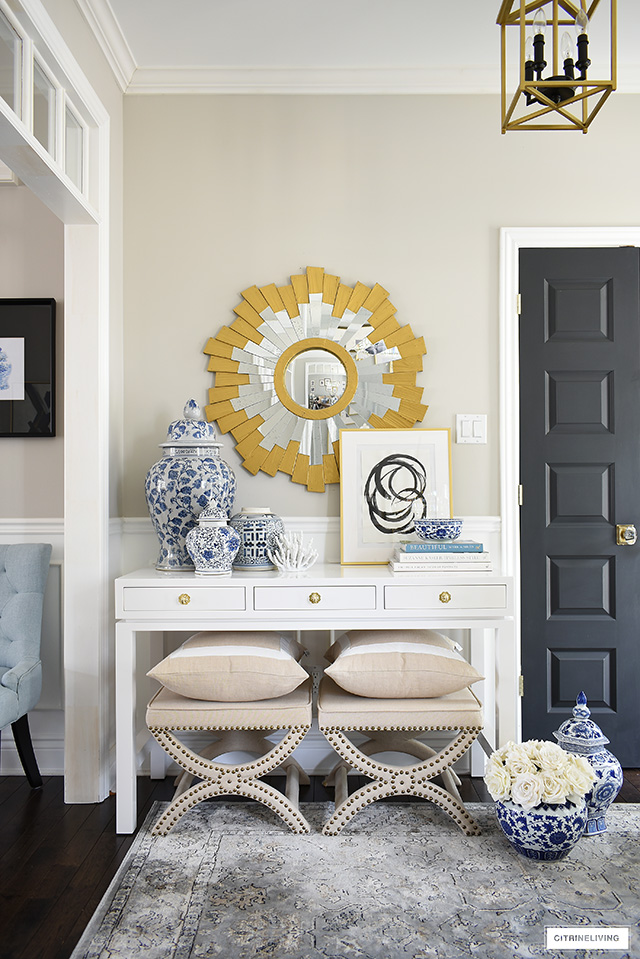 A beautifully styled console table featuring blue and white chinoiserie pieces paired with abstract artwork, design books and a gold sunburst mirror.