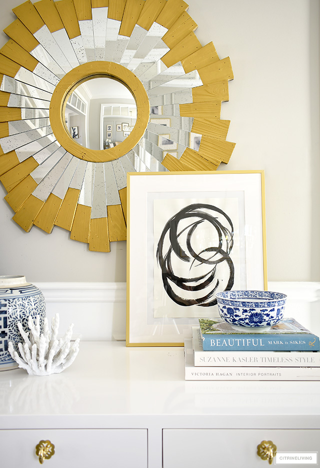 A chic and pretty console table vignette with abstract art, blue and white chinoiserie, design books and a pretty coral sculpture.