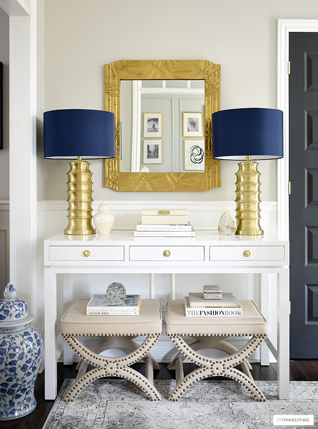 Chic and modern console table styling ideas - a pair of brass lamps, design books and upholstered stools are always great design choices!