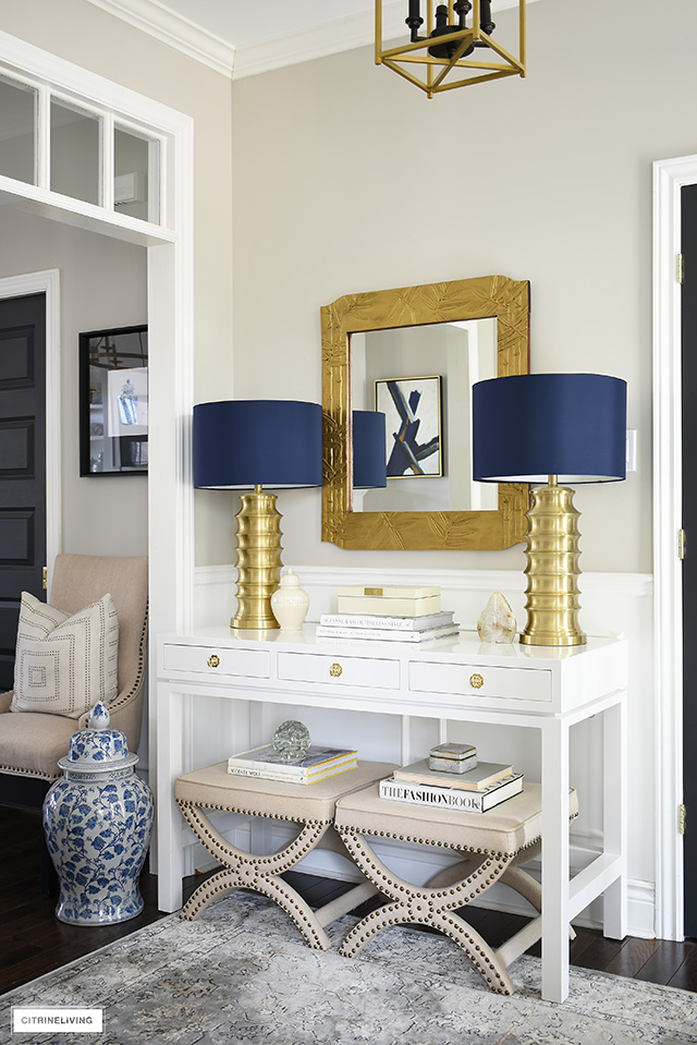 Contemporary and chic console table styling featuring brass lamps with navy shades, a high gloss white table and upholstered stools. Create a sophisticated statement anywhere in your home!
