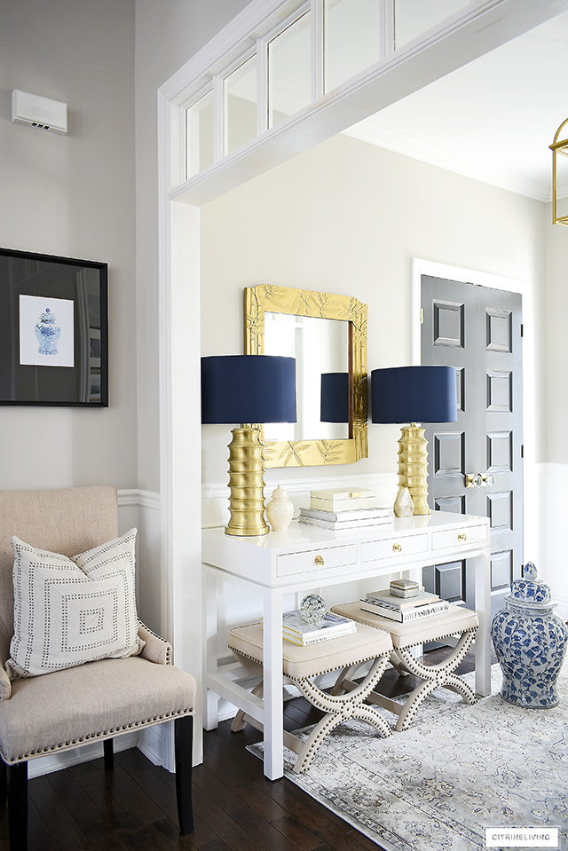 Gorgeous entry with a chic consolable styled with contemporary elements - a pair of brass lamps, upholstered stools and chic accessories make a bold statement!!