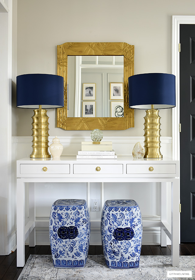 A chic pair of brass lamps and blue and white garden stools add instant style to this console table.