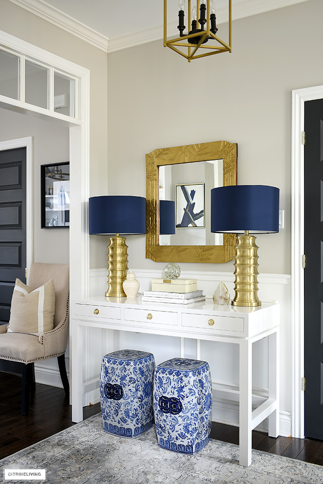 Modern and chic console table styling ideas - brass statement lamps, blue and white garden stools and neutral accessories are elegant and sophisticated.