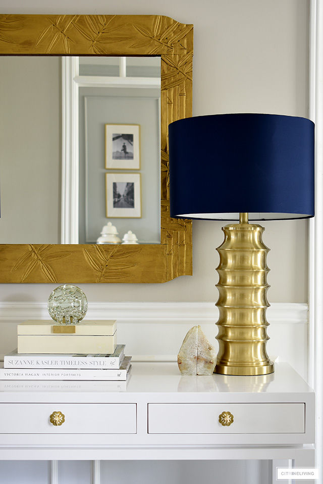 Styling with chic and timeless pieces - brass lamp and mirror, white console table and design books. Add some beautiful accessories to complete the look!