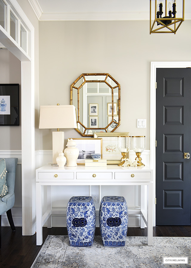Style a console table with a coastal-chic look, layered with neutral accessories together with a pop of color.