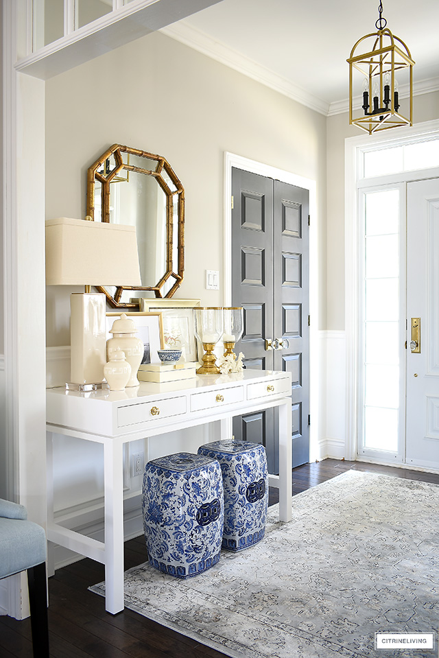 A coastal-chic console table styled with blue and white garden stools and layers of neutral accessories.