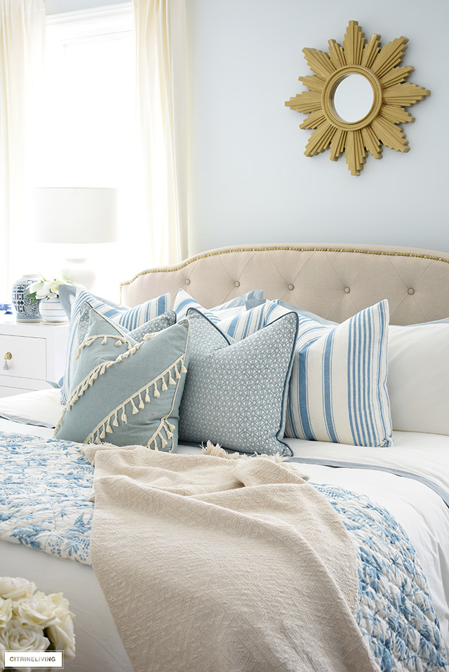 Luxe bed with layered blue printed throw pillows creates an inviting, lush look!
