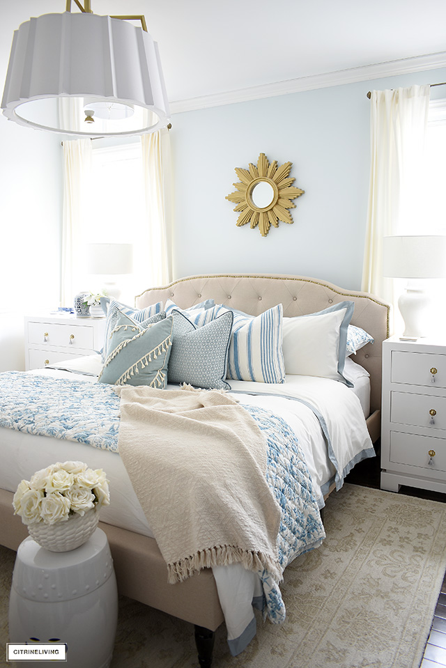 Gorgeous blue and white bed styled with layers of blue hues for a light, airy beach-inspired look.