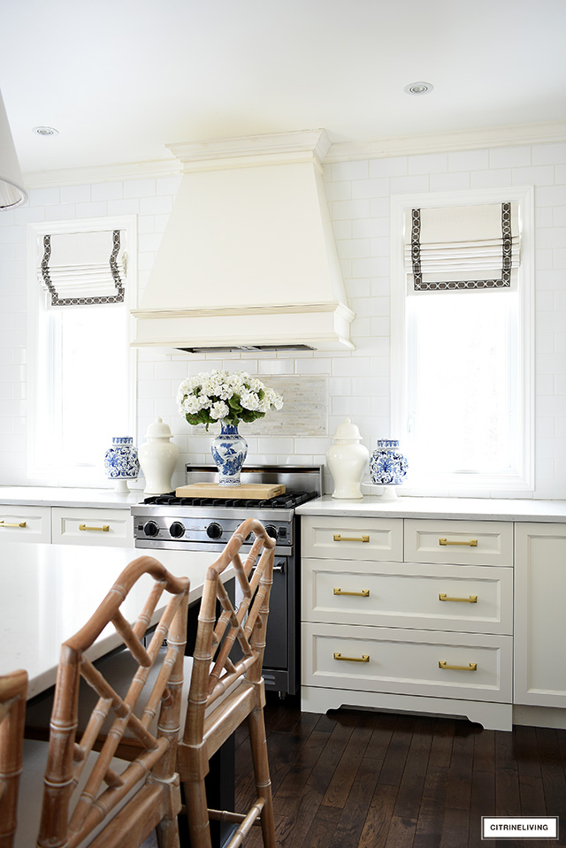 A gorgeous spring decorating statement around this kitchen range with ginger jars, cake stands and pretty faux flowers.