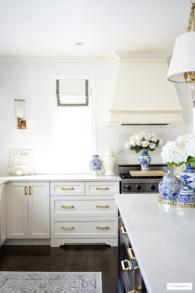 Beautiful kitchen featuring fresh spring decor with pretty faux flowers and blue and white chinoiserie pieces.
