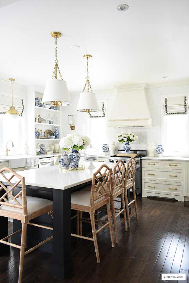 Beautiful white kitchen with black island, Chinese Chippendale barstools, brass lighting and hardware accented with gorgeous blue and white pieces for spring.