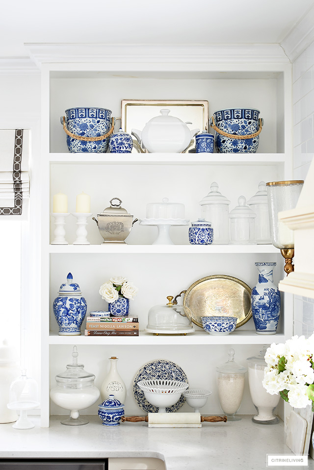 Spring kitchen decorating featuring gorgeous shelf styling using blue and white pieces mixed with cook books, apothecary jars, cake stand and silver pieces.
