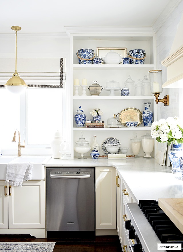 Beautifully and thoughtfully styled open kitchen shelves for spring with a collection of blue and white chinoiserie pieces, silver pieces, glass apothecary jars and cake stands, and white accents.