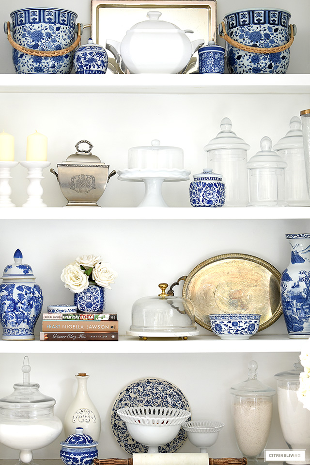 Beautiful open kitchen shelf styling for spring with fresh and vibrant blue and white pieces mixed with silver, white and glass accessories.