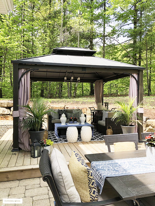 Outdoor living room with beautifully furnished gazebo decorated with garden stools, lanterns, ginger jars and pillows.