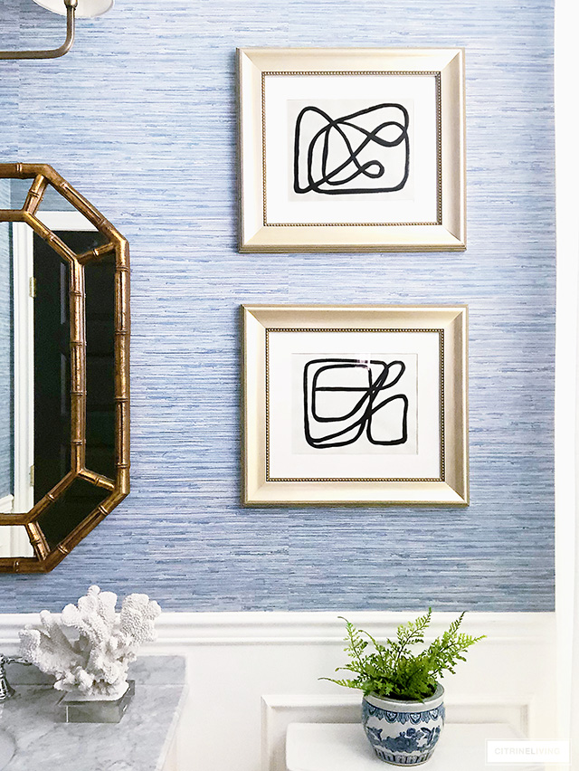 Coastal-chic bathroom with gold framed abstract linear art.
