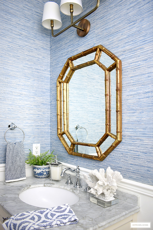 Coastal-chic bathroom with a gold Hollywood regency mirror, vanity with grey marble top and coast accents.