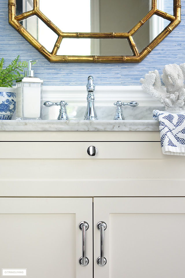 White bathroom vanity with silver hardware and accessories.