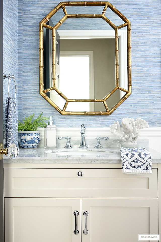 Chic bathroom decor with gold regency style mirror, blue grasscloth wallpaper and coastal accents.