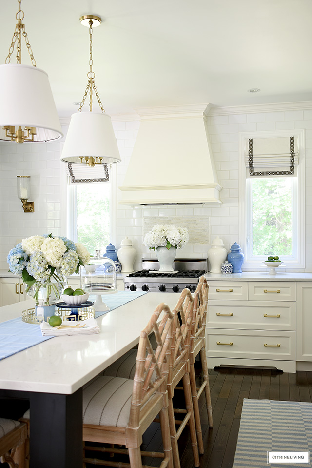 White kitchen decorated for summer with blue and white ginger jars and hydrangeas.