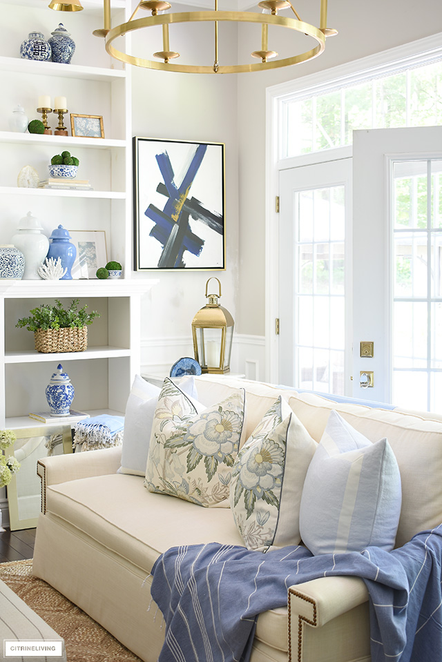 Summer decorating at it's best! Pretty blue ginger jars, baskets, greenery, floral and light blue pillows, a beautiful throw...gorgeous details create a breezy coastal look!