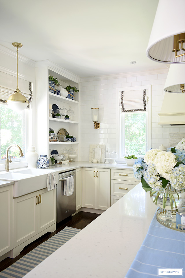 Open kitchen shelves with blue and white chinoiserie and greenery for summer.