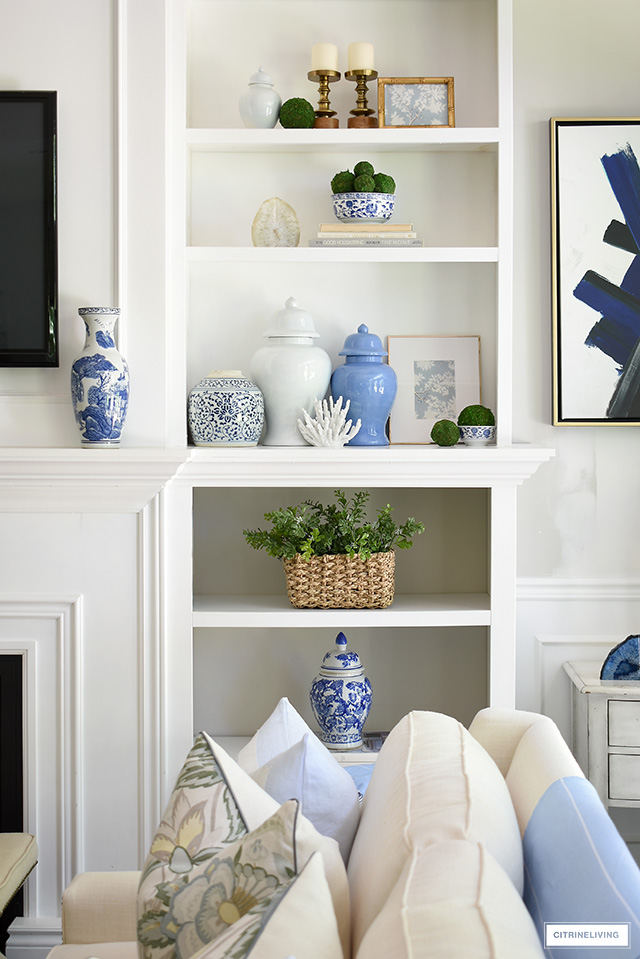 Gorgeous styled bookshelves with blue ginger jars, blue and white bowls and vases, greenery and natural elements.
