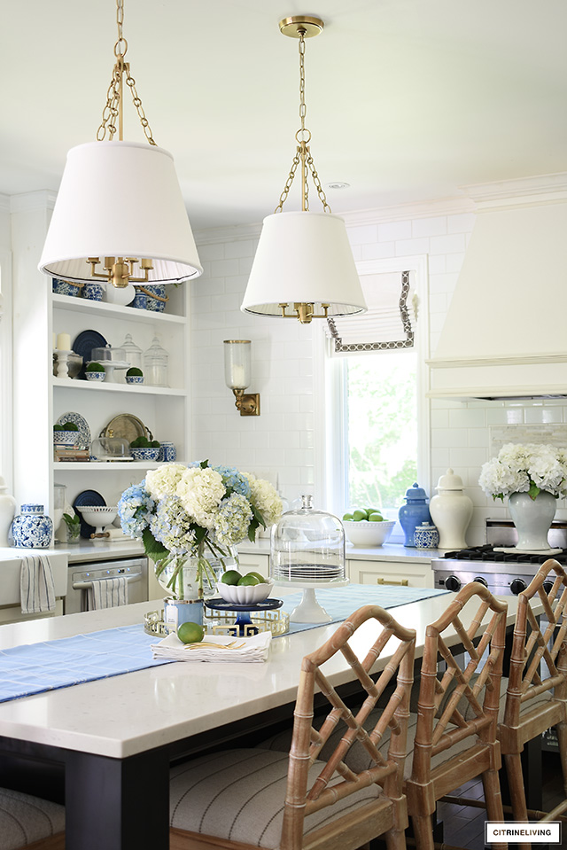 Kitchen island decorated for summer with blue and white hydrangeas.