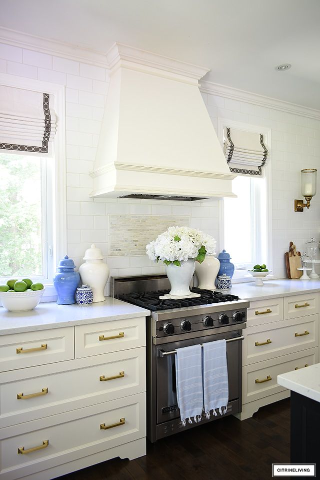 Summer kitchen decorating - ginger jars flanking the stove with a faux hydrangea arrangement styled on a marble tray on top.
