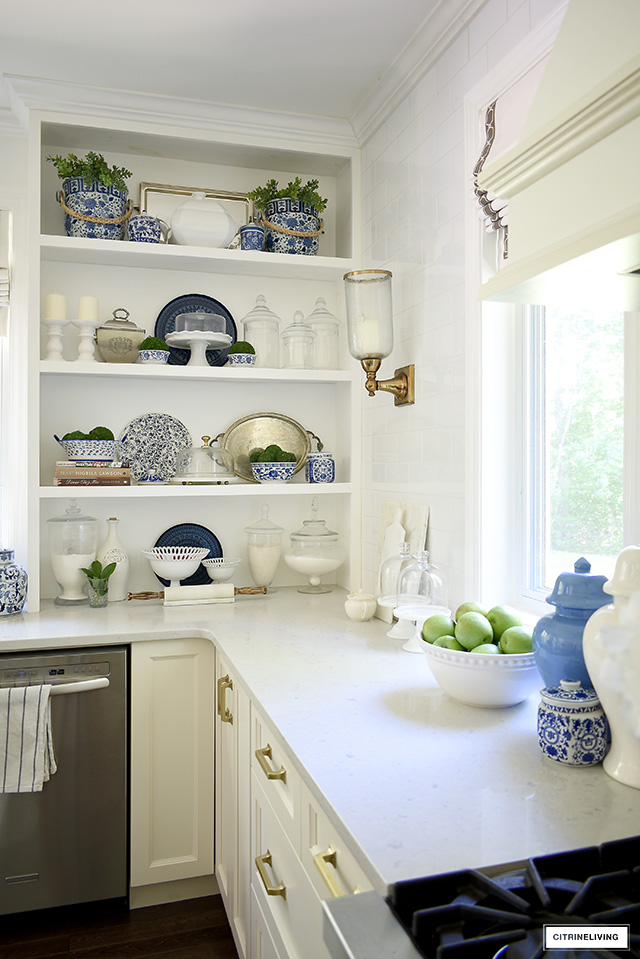 Summer decorating in the kitchen - shelving with blue and white bowls, dishes and jars, with touches of greenery for summer.